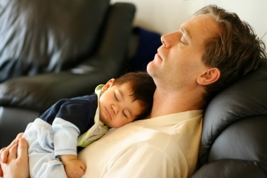 father and son asleep on a leather couch